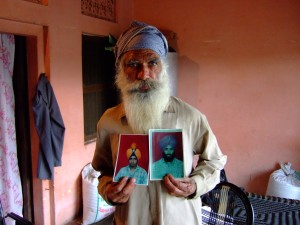 A man shows photos of his sons who were disappeared during the Indian government's counterinsurgency campaign in Punjab.